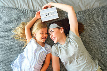 Hold you tight. Cute loving emotional woman hugging her daughter  tight while spending the morning in bed and feeling happy. Nose to nose. Holding light letterbox with letter love