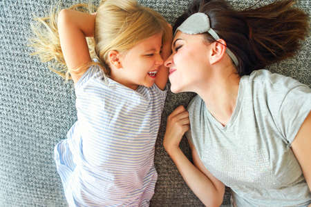Hold you tight. Cute loving emotional woman hugging her daughter  tight while spending the morning in bed and feeling happy. Nose to nose Imagens