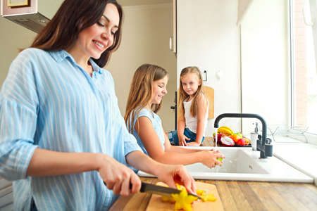 Beautiful little girls with they mother in the kitchen preparing a fresh fruit salad