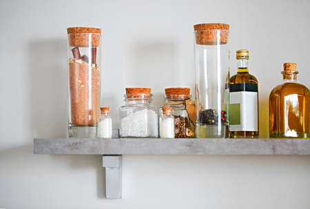 Selective focus of arranged jars with various spices and olive oil on kitchen shelf  Reklamní fotografie