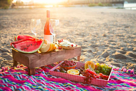 Outdoor picnic with rose wine, fruits, nuts meat and cheese 免版税图像