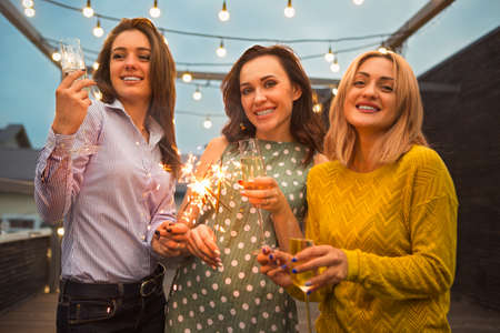 Group of partying girls with flutes with sparkling wine and bengal fire having fun on the party Standard-Bild