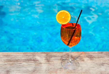 Glass of Aperol Spritz cocktail on the pool nosing at the tropical resort
