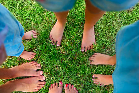 Happy young family spending time outdoor on a summer day. Feet on the grass. Top view