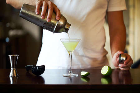 Barman at work, preparing cocktails. Pouring martini to cocktail glass. Service and beverages concept