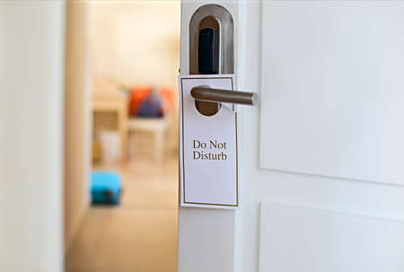 Do Not Disturb sign on hotel room's door. Close up
