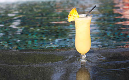 Glass of pinacolada cocktail standing on the swimming pool ledge in an tropical resort Stock Photo