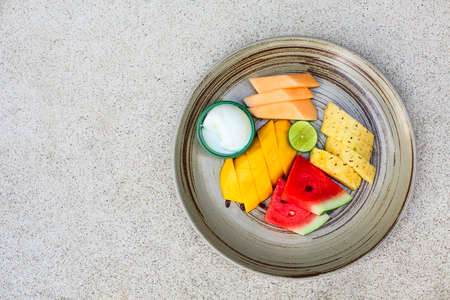 Colorful summer fruit platter with watermelon, mango, pineapple, lime, melon and icecream