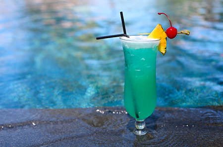 Glass with a bright blue lagoon cocktail by the pool. Luxury resort on tropical island