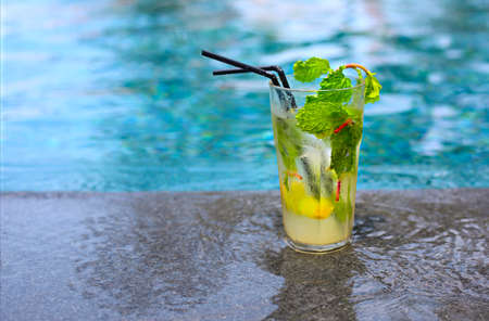 Mojito cocktail at the edge of a resort pool. Concept of luxury vacation. Outdoor pool background