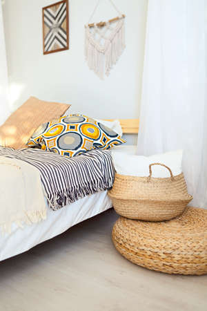 White and beige bedroom in boho style with macrame on the wall Banque d'images