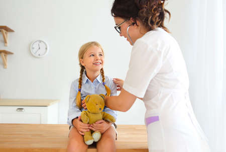 Young smiling female doctor and her little patient with teddy bear