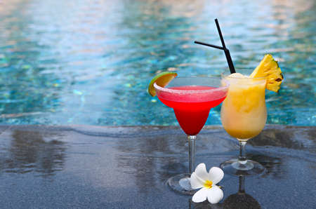 Strawberry daiquiri and pina colada on the pool background, selective focus. Tropical holidays