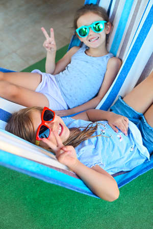 Two little happy girls playing on hammock in summer day