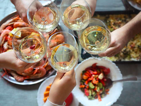 The top view on a table with food and toast with white wine. Gratin, salad and seafood on the table  Фото со стока
