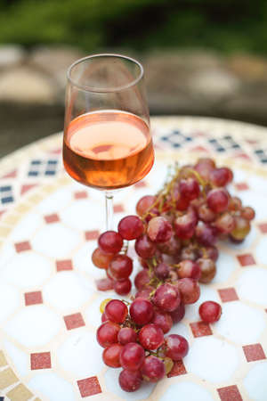 One glass of rose wine in autumn vineyard on marble table. Harvest time, picnic or wine fest theme