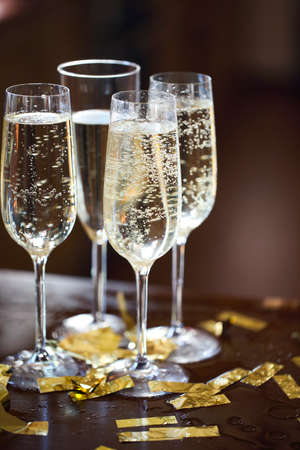 Champagne Flutes In Golden Sparkle Background with golden confetti. Close up
