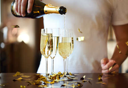 Champagne Flutes In Golden Sparkle Background with golden confetti. Man pouring sparkle wine. Close up