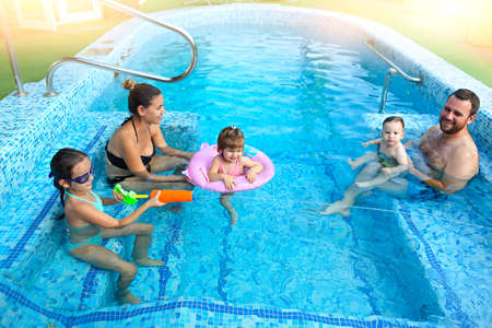 Happy young family with little kids having fun together in the pool