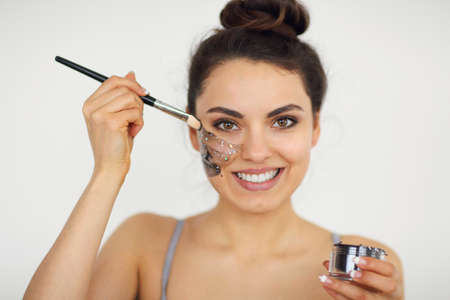 Young woman applies a magnetic dark mask on her face with a brush