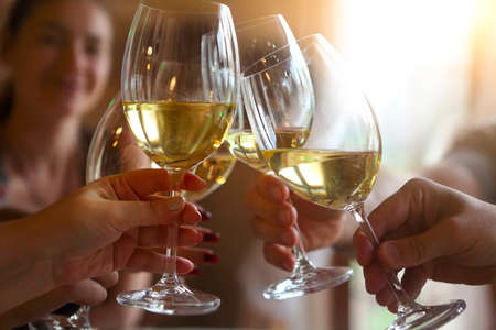 Group of friends enjoying evening drinks. Close up of toast with white wine