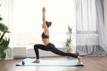 Smiling woman in sportswear exercising on fitness mat and looking at camera in living room 版權商用圖片