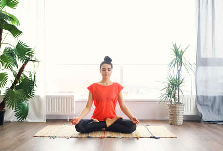 Attractive young brunette woman exercising and sitting in yoga lotus position while resting at home 版權商用圖片