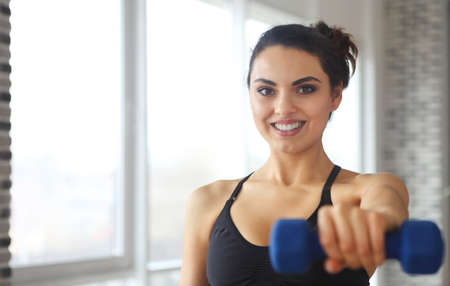Young attractive sportswoman doing fitness exercises at sport gym