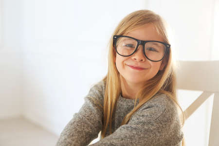 Smiling cute little girl with black eyeglasses over white background. Education, school, childhood, people and vision concept Foto de archivo
