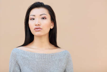 Beauty fashion portrait of sensual asian young woman with dark long hair in cozy knitted grey sweater on the beige background