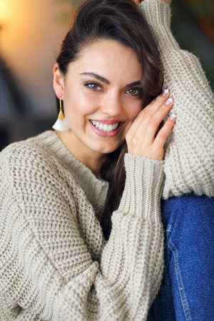 Portrait of a young happy beautiful brunette woman in warm clothings at home