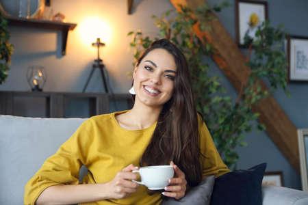 Hermosa mujer morena sonriente tomando café en casa Foto de archivo