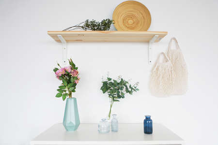 Wooden shelf and white commode with vases on it on light wall background 版權商用圖片