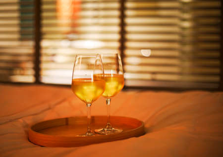 Two glasses of white wine in bed on the blurred background. Copy space