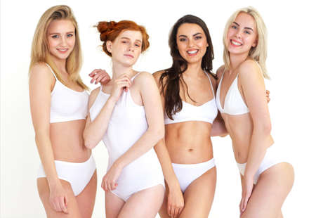 Cheerful young multiethnic women in white lingerie together. Body positivity concept