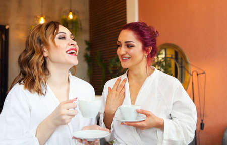 Two women in white robes drinking tea after spa treatments and talking