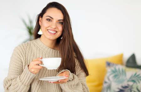 Beautiful smiling brunette woman drinking coffee at home 版權商用圖片