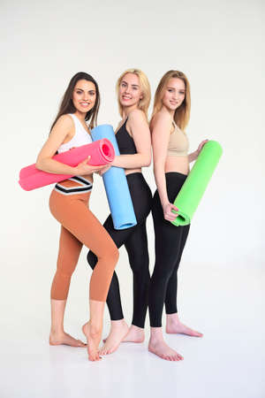 Group of millennial happy attractive slim females standing in a row holding yoga mat resting feels good and healthy after workout. Professional staff instructors at training gym fitness studio concept Banco de Imagens