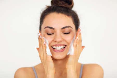 Mooie jonge donkerbruine kaukasische vrouw die haar gezicht met schuim wast