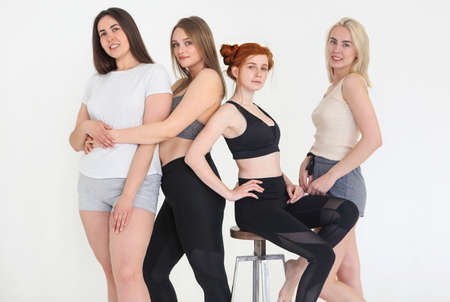 Happy different race women wearing sports top and leggings looks perfect and gathered at fitness studio for training together. Multiracial sporty females together. Body positive concept 版權商用圖片