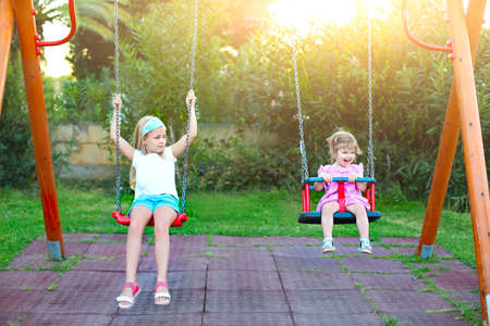 Children playing on playground in park. Two little sisters on the swing 版權商用圖片