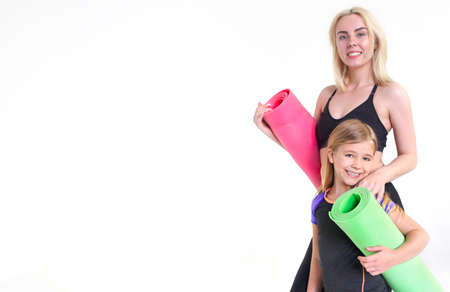 Mother and daughter holding yoga mats, isolated on white. Sport, family, health concept