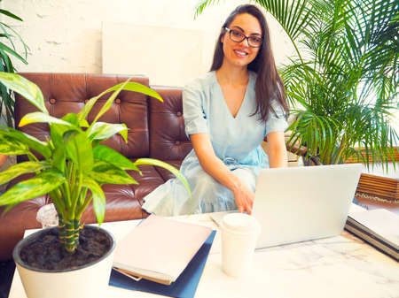 Beautiful mixed race woman sitting in a coffee shop and smiling while using her laptop 版權商用圖片
