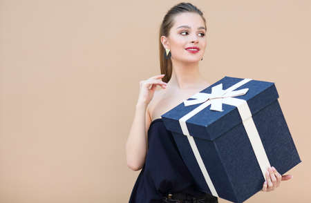 Surprised cute girl in navy blue clothes holding big gift box isolated on beige 版權商用圖片