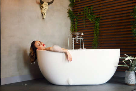 Portrait of the happy young woman relaxing in bathtub