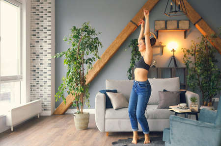 Happy mixed race young woman listening to music with wireless portable speaker. Hispanic hipster girl dancing to rhythm and singing along melody at home