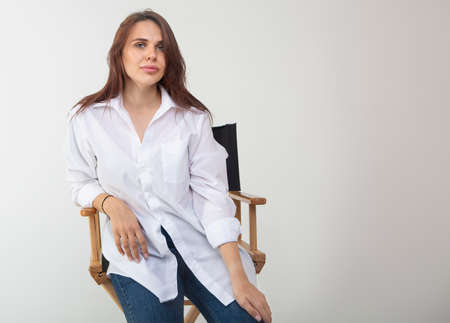 Beautiful brunette woman posing at studio in white shirt, sitting on chair