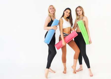 Group of millennial happy attractive slim females standing in a row holding yoga mat resting feels good and healthy after workout. Professional staff instructors at training gym fitness studio concept