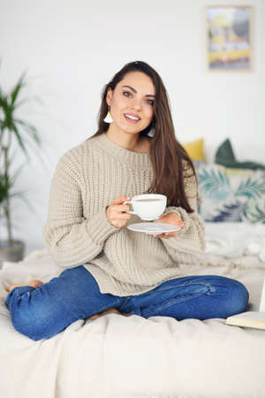 Young happy brunette woman with book wearing sweater at home 版權商用圖片