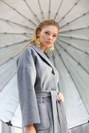 High fashion portrait of young elegant woman in Grey coat, black pants, black ankle boots and gold earrings